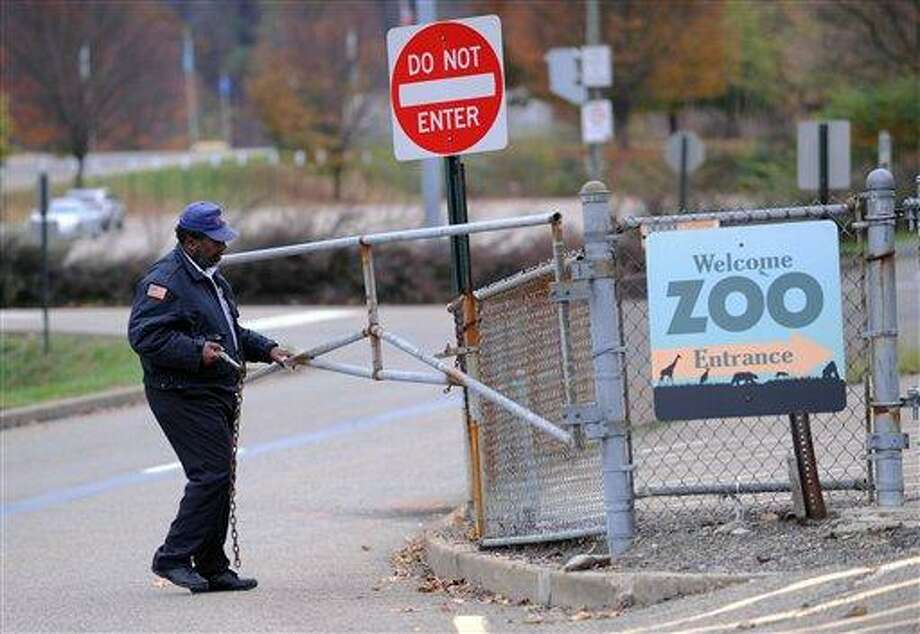 A security guard closes the gate at the Pittsburgh Zoo, where zoo officials say a young boy was killed after he fell into the exhibit that was home to a pack of African painted dogs, who pounced on the boy and mauled him, Sunday, Nov. 4, 2012. It's not clear whether he died from the fall or the attack, said Barbara Baker, president and CEO of the Pittsburgh Zoo & PPG Aquarium. (AP Photo/John Heller) Photo: AP / FR48174 AP
