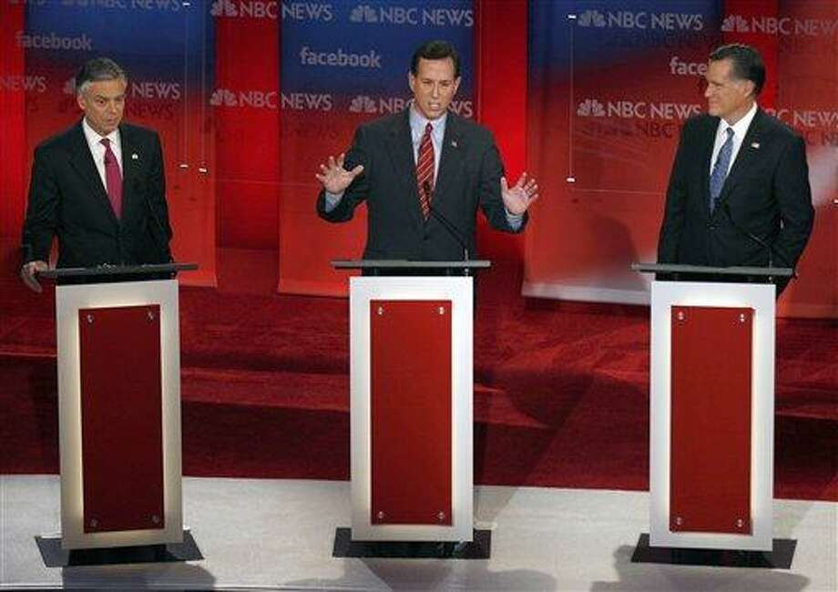 Former Pennsylvania Sen. Rick Santorum, center, answers a question as former Utah Gov. Jon Huntsman, left, and former Massachusetts Gov. Mitt Romney, right, listen during a Republican presidential candidate debate at the Capitol Center for the Arts in Concord, N.H., Sunday. Associated Press Photo: AP / AP