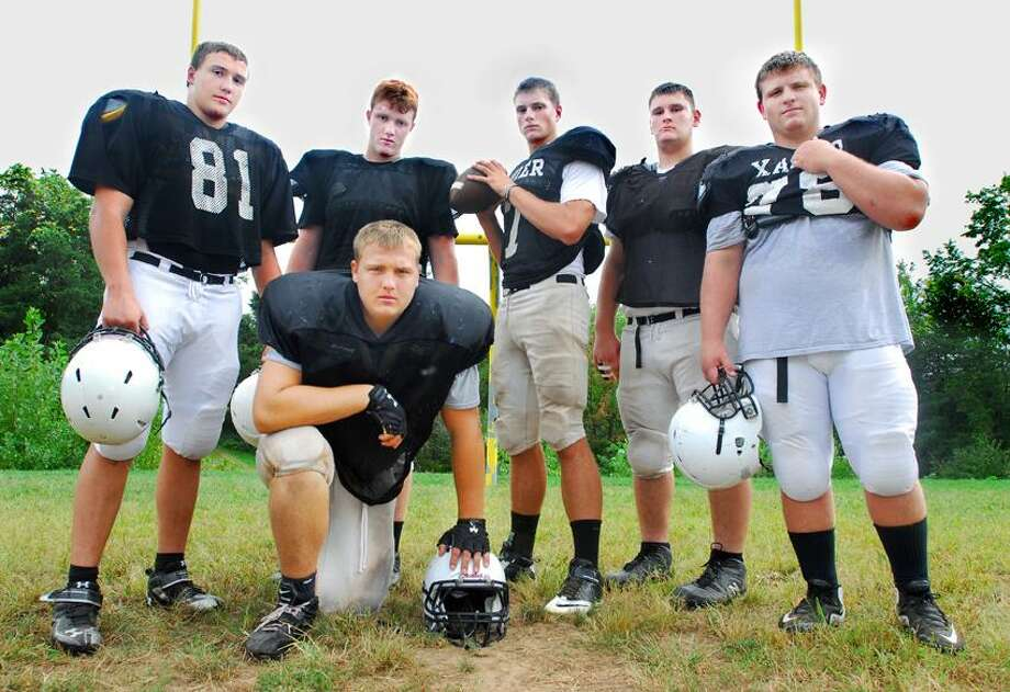 (Catherine Avalone/The Middletown Press) Xavier seniors Kevin Dean, Jonah Dorsey, quarterback Tim Boyle, Ben Lisle, Zac Creeron, and center Max Schumann (kneeling) at practice Tuesday.