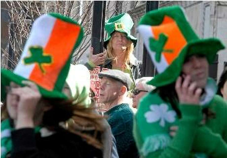 File photo: Gail Tucci, of Oxford, uses a street light on Chapel Street for a better vantage point to see the St. Patrick's Day parade Sunday in New Haven. Photo by Brad Horrigan/New Haven Register