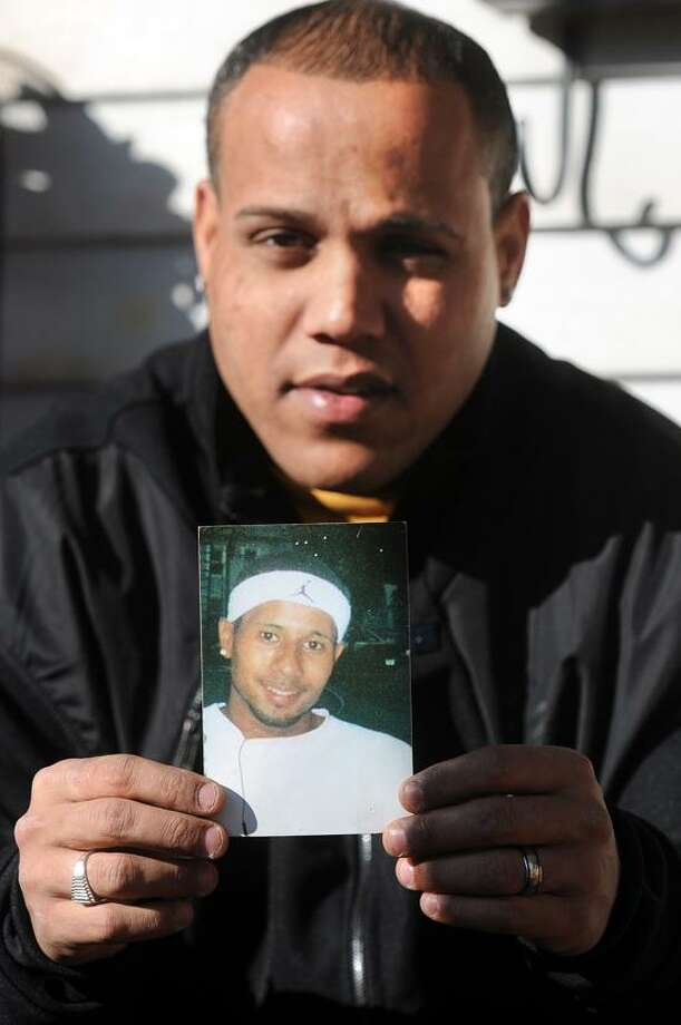 Franklyn Cruz of Meriden holds a picture of his brother, Jose Ortiz, who disappeared in 2005 in New Haven.   Peter Casolino/Register