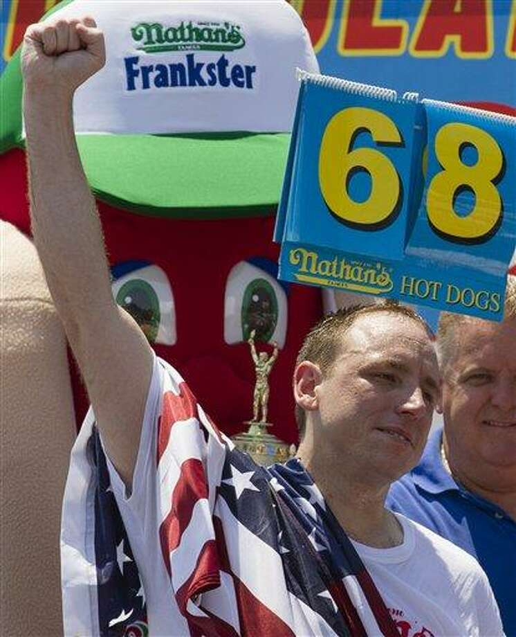 Five-time reigning champion Joey Chestnut celebrates after he wins his sixth Nathan's Famous Hot Dog Eating World Championship with a total of 68 hot dogs and buns, Wednesday, July 4, 2012, at Coney Island, in the Brooklyn borough of New York. (AP Photo/John Minchillo) Photo: AP / AP