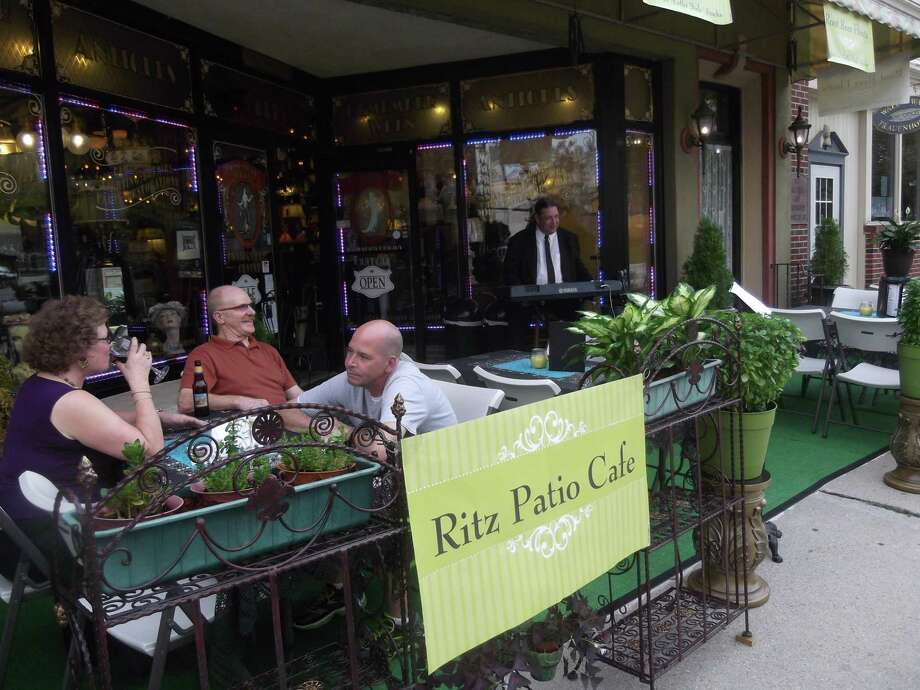 RICKY CAMPBELL/ Register Citizen Torrington's own Dr. Mike entertained outdoor dining guests Thursday night outside the Torrington Gold Exchange. The outdoor dining was developed to invite residents to continue visiting downtown despite Main Street Marketplace's seasonal departure.
