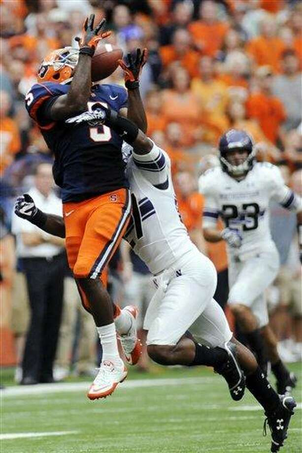 AP Photo/Hans Pennink Syracuse's Marcus Sales (5) makes a catch while being defended by Northwestern's Jared Carpenter (27) during the fourth quarter of an NCAA college football game in Syracuse, N.Y., Saturday, Sept. 1, 2012. Northwestern won 42-41. Photo: AP / FR58980 AP
