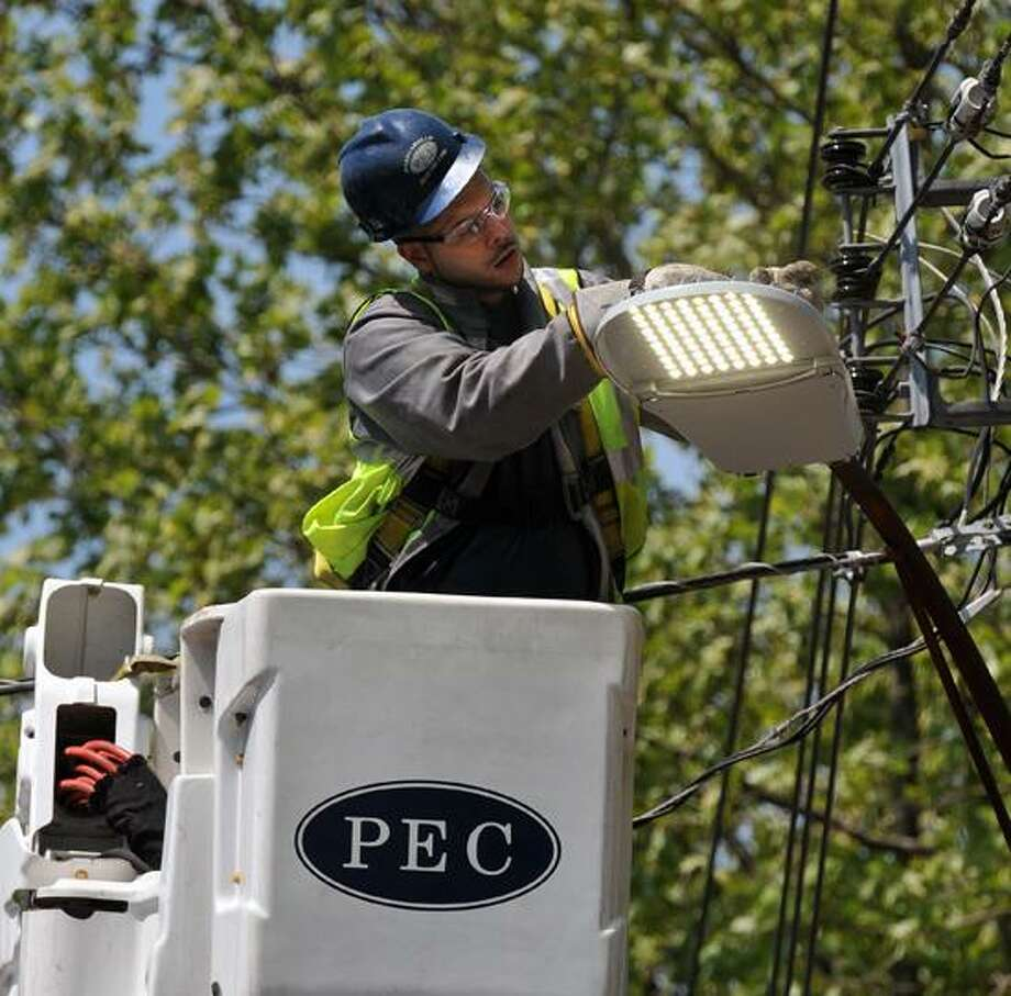 Fernando Casanova of Pasquariello Electric turns on one of the newly installed LED lights along Lilac Street in New Haven. Peter Casolino/New Haven Register