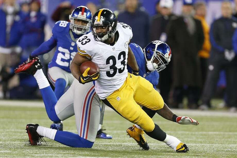Pittsburgh Steelers running back Isaac Redman (33) breaks a tackle by New York Giants free safety Antrel Rolle (26) during the second half of an NFL football game Sunday, Nov. 4, 2012 in East Rutherford, N.J. The Steelers won the game 24-20.  (AP Photo/Julio Cortez) Photo: AP / AP2012