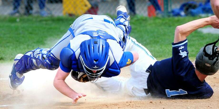 Seymour catcher Mike Conlan (left) flies into the air after tagging Mike Palmquist (right) of Ansonia out at the plate on Monday. Ansonia won 7-5. Photo by Arnold Gold/New Haven Register