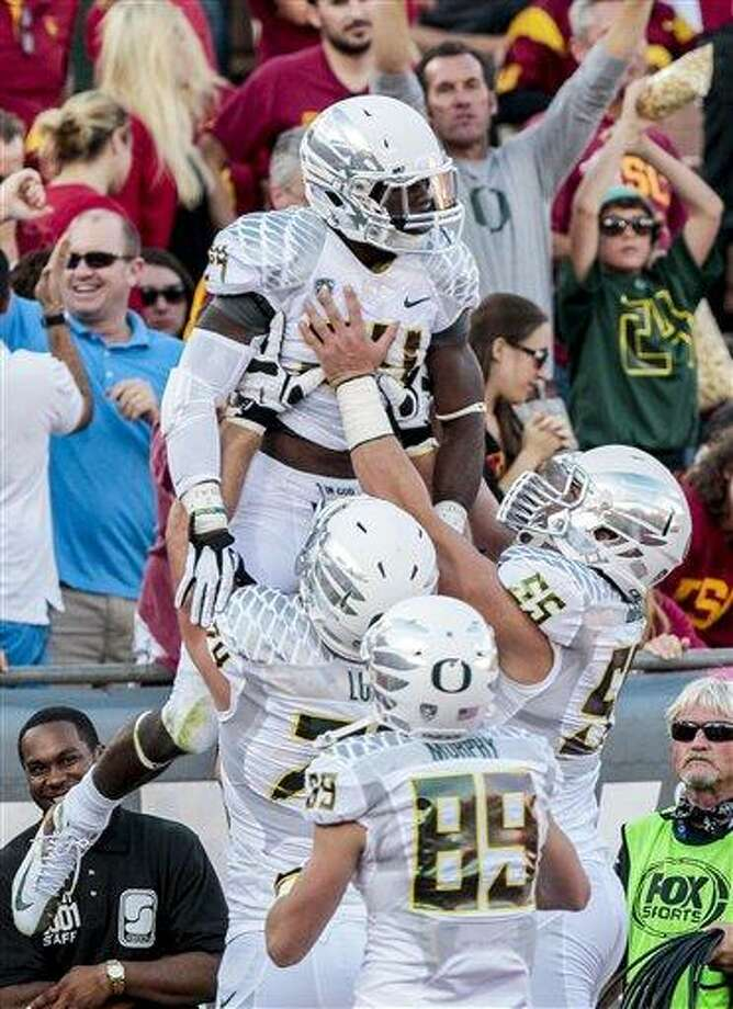 Oregon running back Kenjon Barner, top, celebrates with teammates after scoring during the first half of an NCAA college football game against Southern California, Saturday, Nov. 3, 2012, in Los Angeles. (AP Photo/Bret Hartman) Photo: AP / FR139655 AP