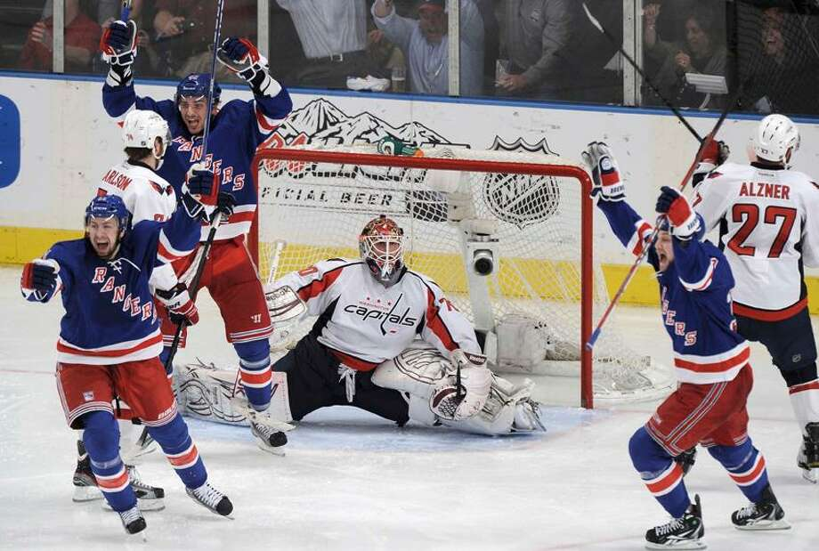 New York Rangers' Derek Stepan (L), Artem Anisimov, and John Mitchell (2nd R) celebrate after Marc Staal, not seen, scored on Washington Capitals goalie Braden Holtby in the overtime period during Game 5 of their NHL Eastern Conference semi-final playoff hockey series in New York, May 7, 2012. REUTERS/Ray Stubblebine Photo: REUTERS / X00272