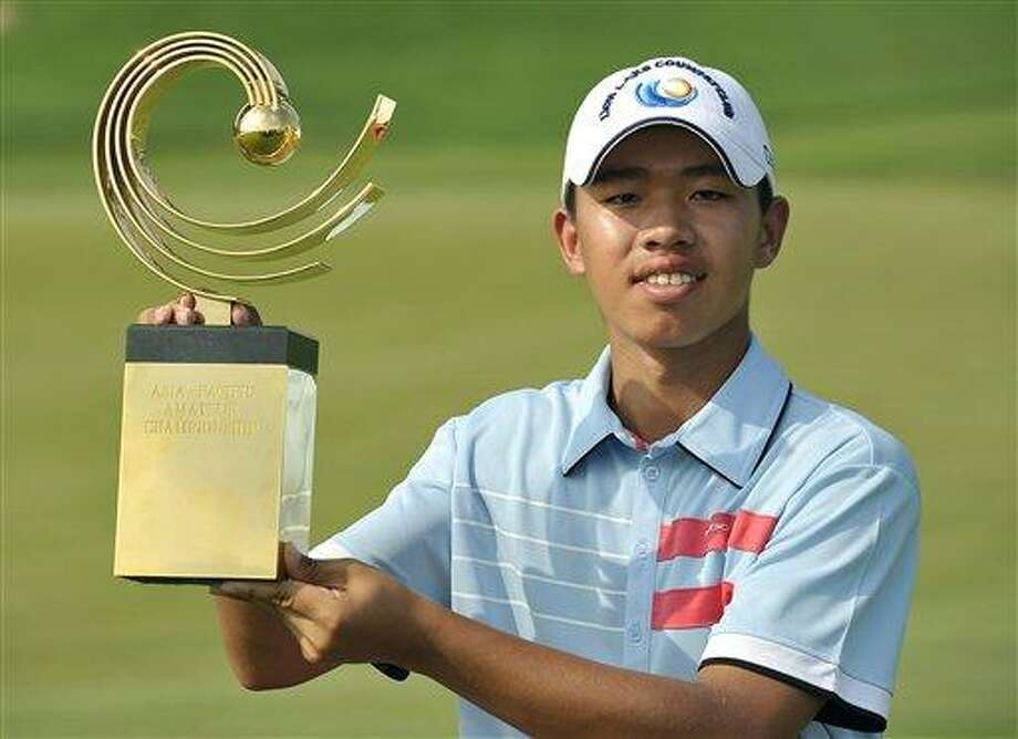 Guan Tianlang of China poses with the winner's trophy at the Asia-Pacific Amateur Championship at Amata Spring Country Club, in Chonburi, Thailand Sunday, Nov. 4, 2012. (AP Photo/AAC, Paul Lakatos) NO LICENSING Photo: AP / AAC