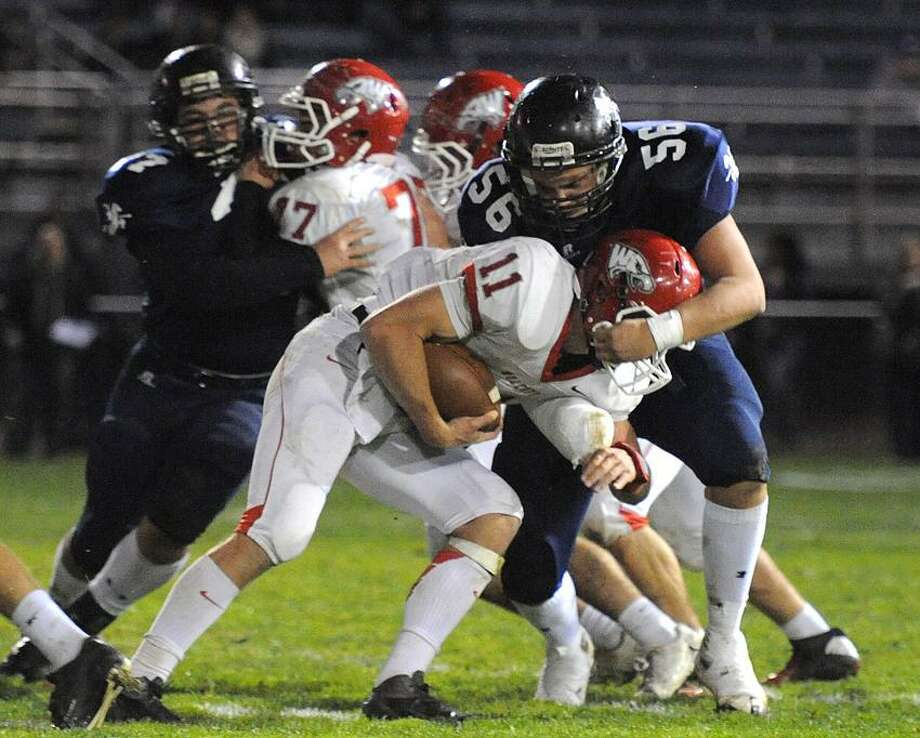 Ansonia-- Ansonia's Matthew Simon puts a stop on Wolcott QB Michael Nicol in the backfield during the first quarter. Photo--Peter Casolino/New Haven Register. 11/02/12