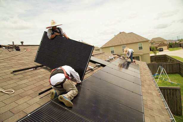 Workers from Alba Solar install solar panels in Katy Texas.
