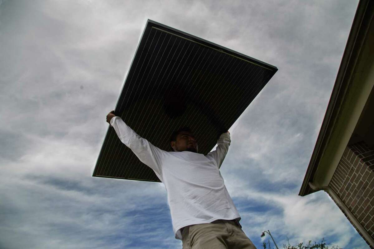 Workers install solar panels on a home in Katy in June. (David A. Funchess / Houston Chronicle )