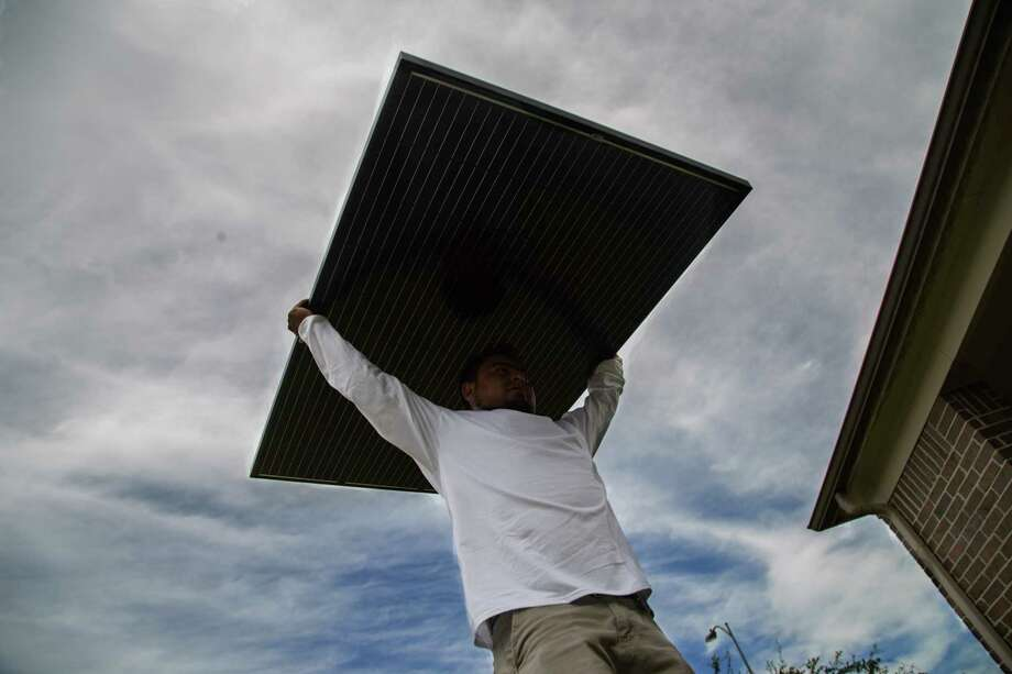 Workers install solar panels on a home in Katy in June. (David A. Funchess / Houston Chronicle ) / Houston Chronicle
