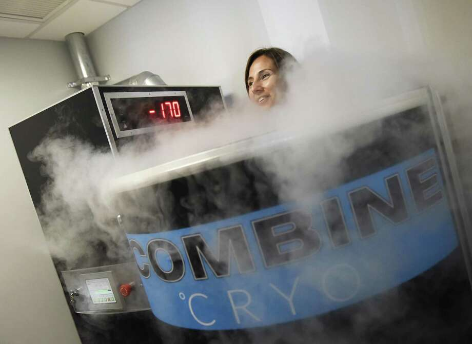 """Operations manager Christina Vitale demonstrates cryotherapy in the Cryosauna at Combine Training in Greenwich, Conn. Tuesday, July 18, 2017. Cryotherapy exposes the body to extremely low temperatures for a short period of time and is said to prompt quick recovery after a workout and release endorphins to give a feeling similar to a """"runner's high."""" Photo: Tyler Sizemore / Hearst Connecticut Media / Greenwich Time"""