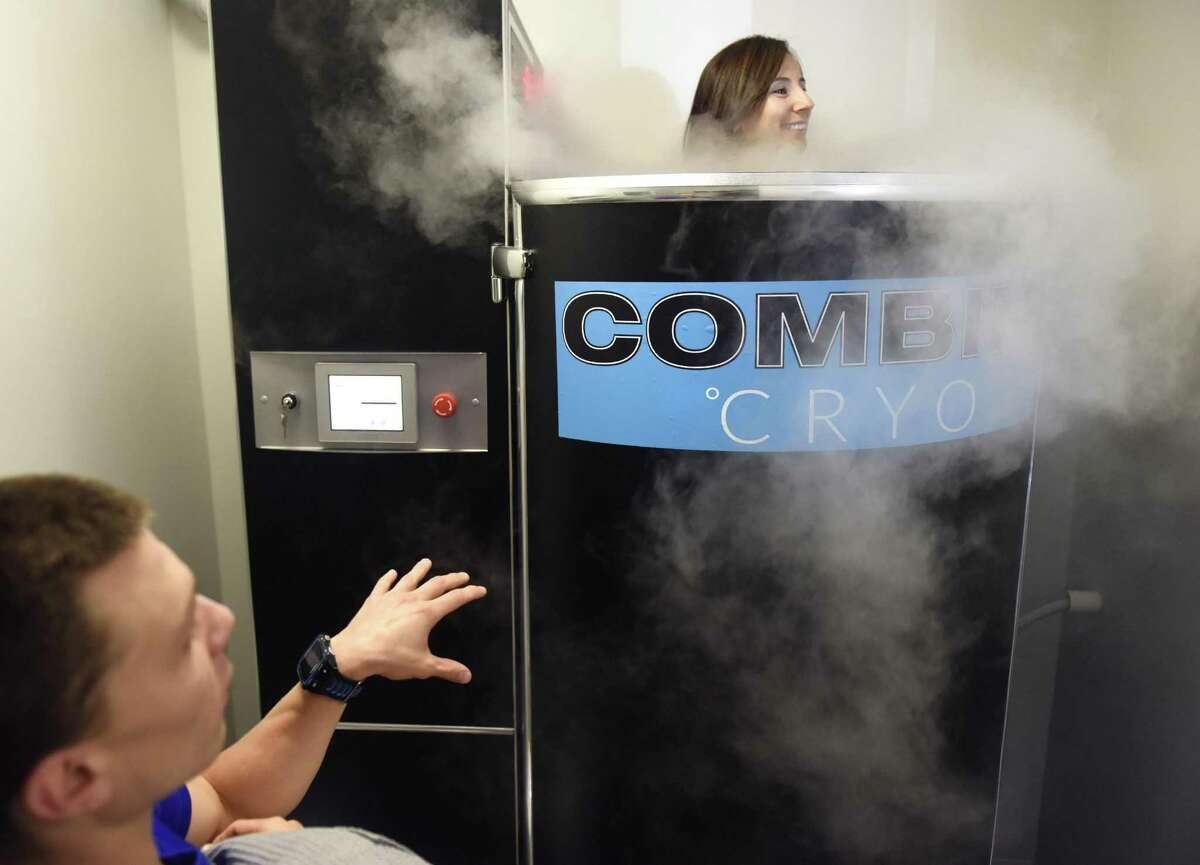 Cryotherapy supervisor Max Tremain assists operations manager Christina Vitale in the Cryosauna at Combine Training in Greenwich, Conn. Tuesday, July 18, 2017. Cryotherapy exposes the body to extremely low temperatures for a short period of time and is said to prompt quick recovery after a workout and release endorphins to give a feeling similar to a