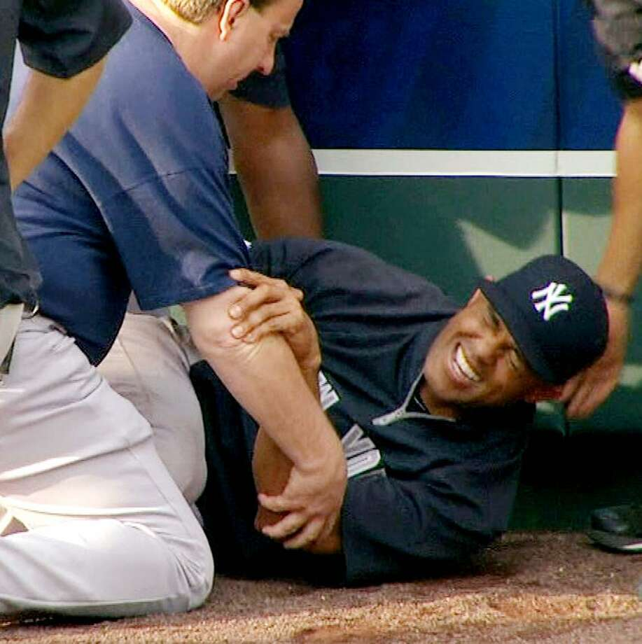 In this image taken from video, New York Yankees' Mariano Rivera, center, grimaces after twisting his right knee shagging fly balls during batting practice before a baseball game with the Kansas City Royals, Thursday, May 3, 2012, in Kansas City, Mo. The Yankees closer was later carted off the field and sent for further tests. (AP Photo/YES Network) MANDATORY CREDIT Photo: AP / AP2012