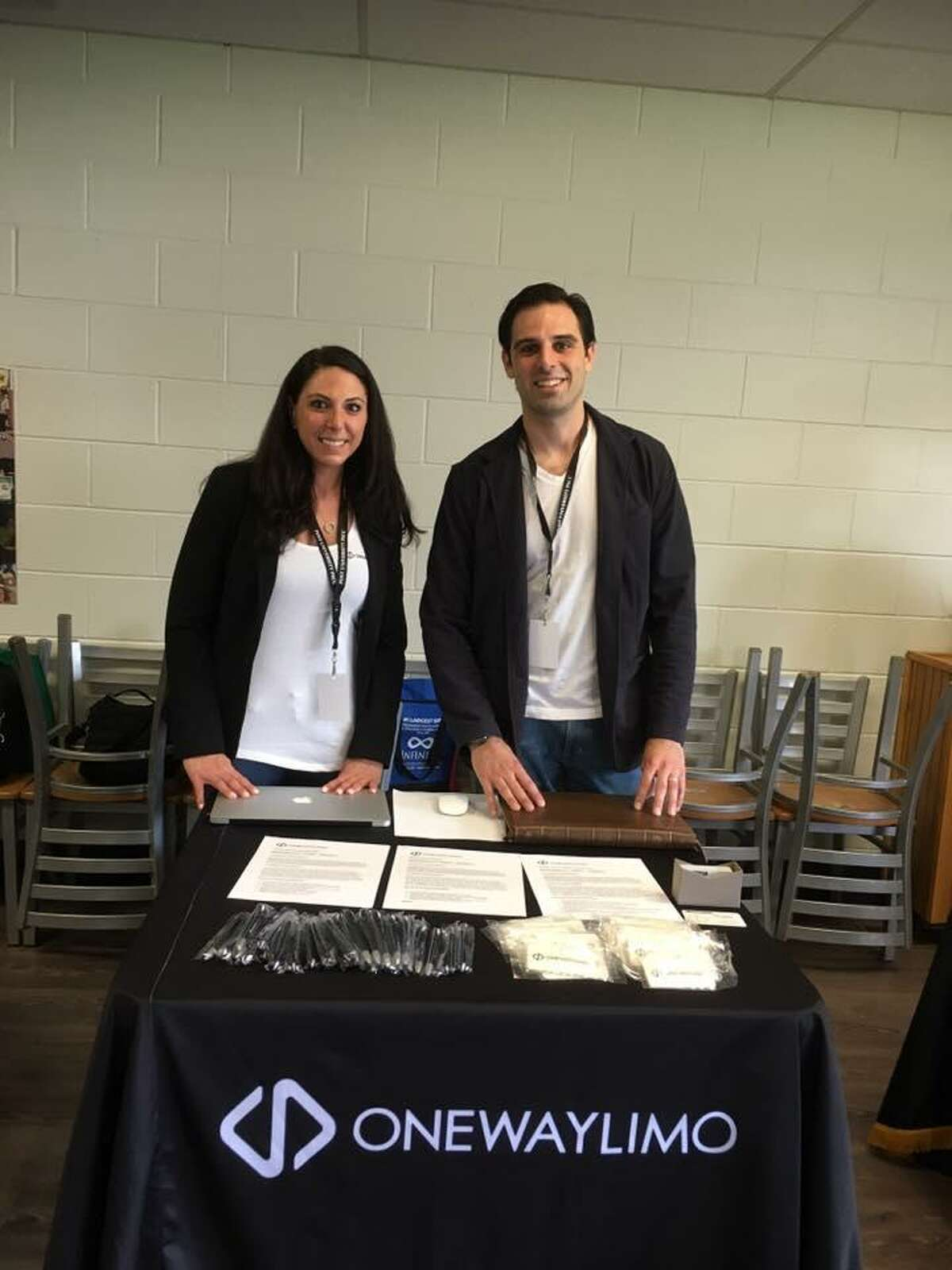Desiree Tavares, chief operating officer at Shelton-based OneWayLimo, and Will Haire, principal partner and director of marketing, pose behind the company's table at the career fair at Post University.