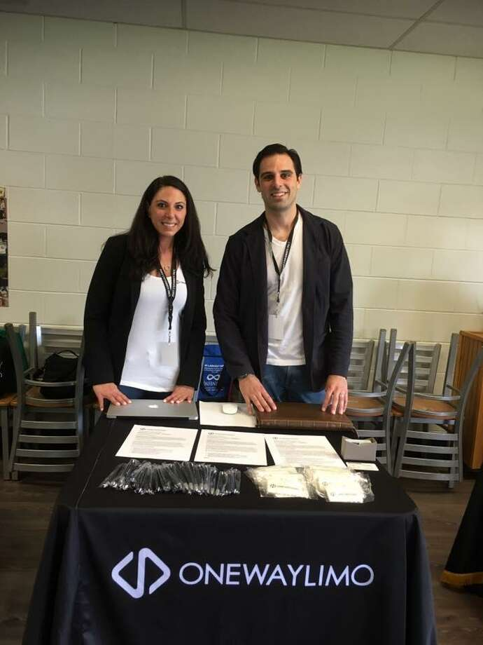 Desiree Tavares, chief operating officer at Shelton-based OneWayLimo, and Will Haire, principal partner and director of marketing, pose behind the company's table at the career fair at Post University. Photo: Contributed Photo / Hearst Connecticut Media