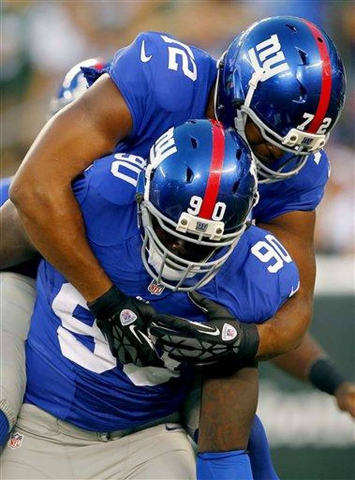 FILE - In this Aug. 18, 2012, file photo, New York Giants defensive end Jason Pierre-Paul (90) celebrates with Osi Umenyiora (72) after sacking New York Jets quarterback Mark Sanchez during the first half of a preseason NFL football game in East Rutherford, N.J. Coughlin knows the Giants can't afford another 9-7 regular season if they want to become the ninth team _ the Steelers did it twice _ to win consecutive titles. The Giants are scheduled to begin their season on Sept. 5 at home against the Dallas Cowboys. (AP Photo/Rich Schultz, File)