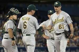 Oakland Athletics manager Bob Melvin takes pitcher John Axford (61) out of the game after he loads the bases in the seventh inning of a baseball game against the Toronto Blue Jays in Toronto, Monday, July 24, 2017. (Fred Thornhill/The Canadian Press via AP)