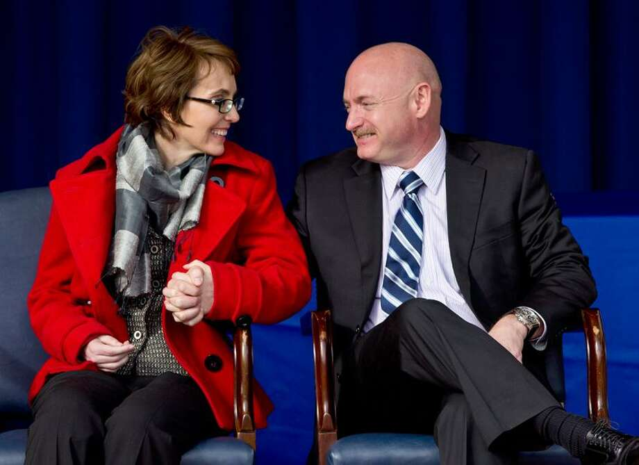 Former Arizona Rep. Gabrielle Giffords and her husband Mark Kelly, attend the unveiling of the USS Gabrielle Giffords at the Pentagon, Friday, Feb. 10, 2012. The Navy has named a ship for Gabrielle Giffords, the recently retired congresswoman from Arizona who is recovering from a gunshot wound to the head received in January 2011.  Associated Press Photo: AP / AP2012