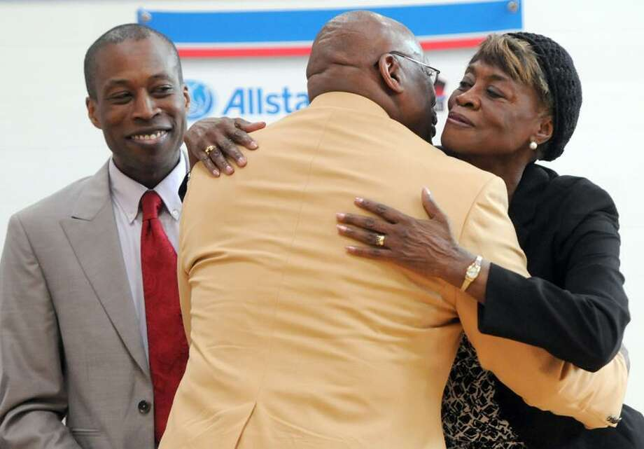 """Floyd Little, National Football League Hall of Fame inductee and former Denver Broncos running back with his nephew Hamden Mayor Scott Jackson as he kisses his oldest sister Betty Jackson Wednesday  5/2/12 at Hillhouse High School, where Little was  honored as a """"Hometown Hall of Famer"""" by the Pro Football Hall of Fame and Allstate Insurance Co.  Photo by Peter Hvizdak / New Haven Register Photo: New Haven Register / ©Peter Hvizdak /  New Haven Register"""