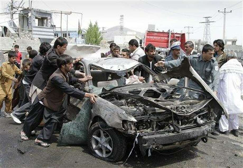 Afghans push a damaged car away from the scene of a militant attack in Kabul, Afghanistan, Wednesday. A suicide car bomber and Taliban militants disguised in burqas attacked a compound housing hundreds of foreigners in the Afghan capital on Wednesday, officials and witnesses said. The Taliban said the attack was a response to President Barack Obama's surprise visit just hours earlier. Associated Press Photo: AP / AP