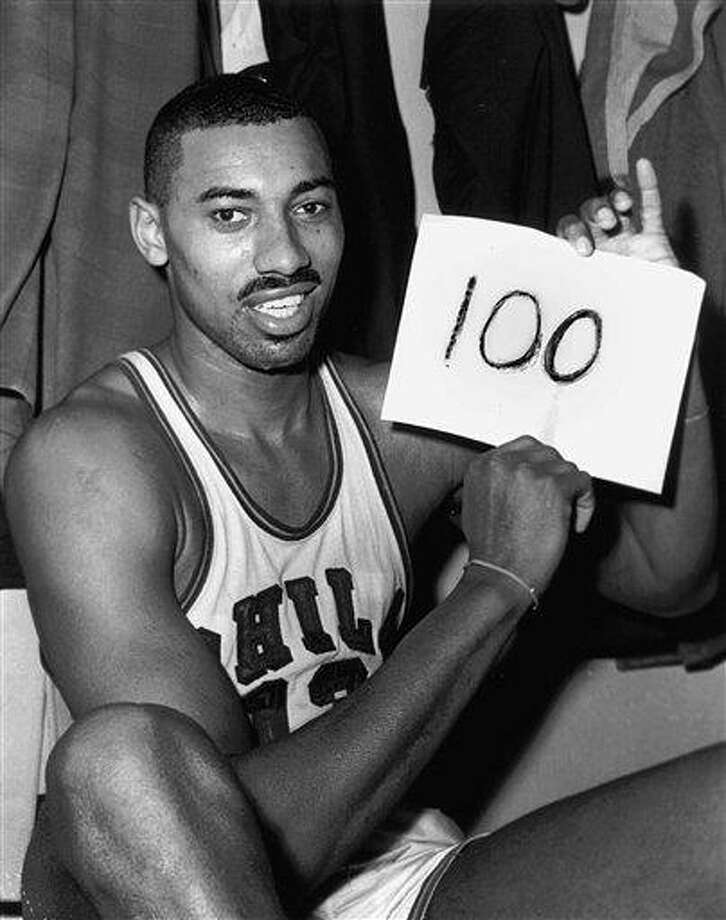 """FILE - In this March 2, 1962 file photo, Wilt Chamberlain of the Philadelphia Warriors holds a sign reading """"100"""" in the dressing room in Hershey, Pa., after he scored 100 points,  as the Warriors defeated the New York Knickerbockers 169-147.  For 50 years, Chamberlain's 100-point night has stood as one of sports magic numbers. (AP Photo/Paul Vathis, File) Photo: ASSOCIATED PRESS / AP1962"""
