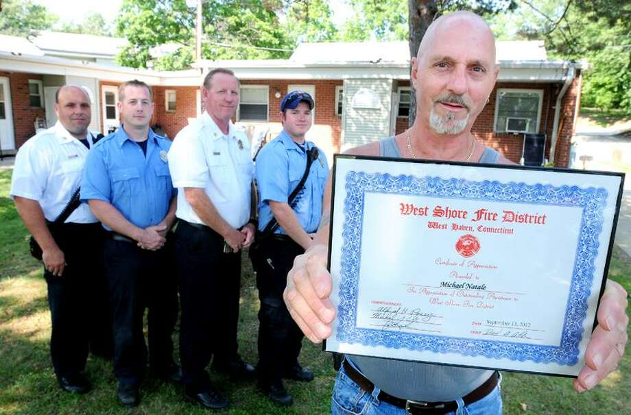 Michael Natale (right) of Killingworth displays a certificate he received from the West Shore Fire District on 8/30/2012 for his work in rescuing and elderly man at Morrisey Manor in West Haven and putting out a fire at the apartment.  In the background are (left to right) Lt. Frank Rasile, Firefighter Collin McBurney, Chief Dave Collins and Firefighter Ryan Nicholls of the West Shore Fire District. Photo by Arnold Gold/New Haven Register