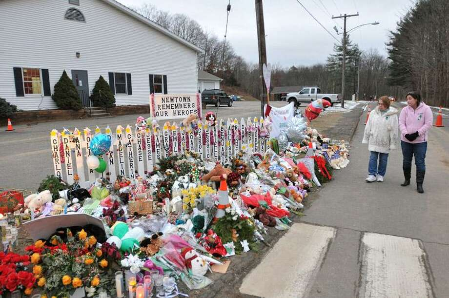 Tami Lawson, right, and her mother, Penny Tanner look at the memorials Wednesday along the driveway of the Sandy Hook Elementary School. Lawson grew up in Newtown and now lives in Golden, Colorado. Her mother still lives in Newtown. Peter Casolino/Register