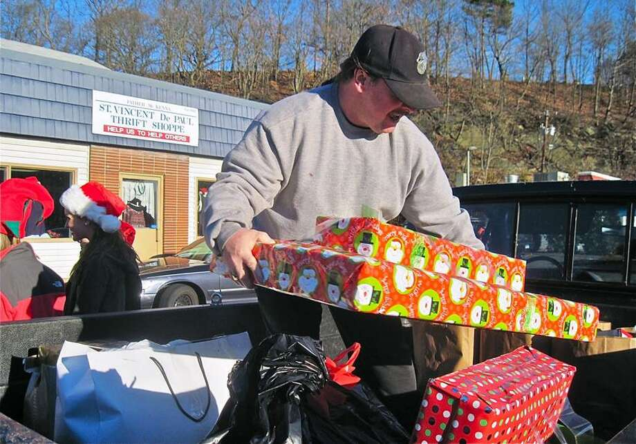 William Smith of Ansonia places Christmas presents for his family in the back of his pickup truck at St. Vincent De Paul Helping Hands of the Valley in Derby. Smith's family of five receives assistance from St. Vincent De Paul. Patricia Villers/Register