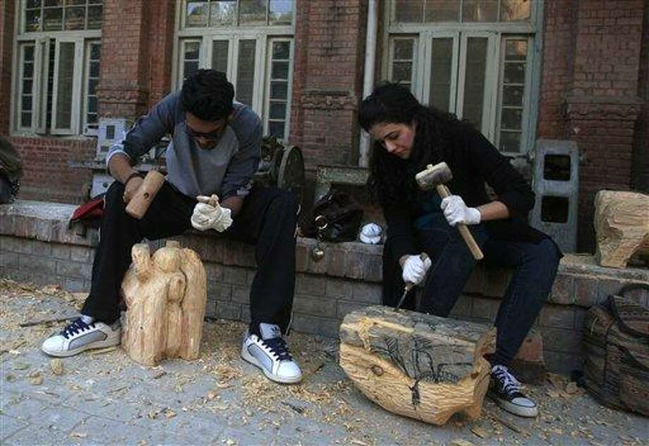 In this photo taken on Tuesday, Dec. 6, 2012, Pakistani students carve wooden statues in the National College of Arts in Lahore, Pakistan. A series of provocative paintings of Muslim clerics in scenes suggesting homosexuality has sparked a moral and legal crisis at Pakistan's leading arts college after extremists threatened violence, declaring that the works insult Islam.(AP Photo/K.M. Chaudary) Photo: AP / AP