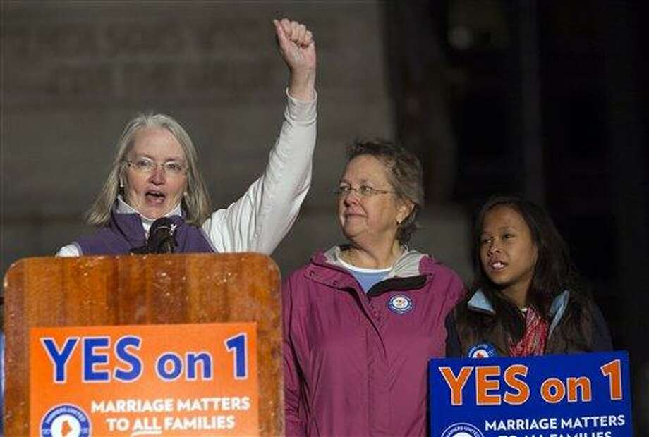 FILE - In this Nov. 1, 2012 file photo, Sarah Dowling, left, speaks at a gay marriage rally, accompanied by her partner of 18 years, Linda Wolfe, and their daughter, Maya Dowling-Wolfe, in Portland, Maine.  Dowling and Wolfe plan to marry after Maine passed a law allowing same-sex marriage, which takes effect at 12:01 a.m., Saturday, Dec. 29, 2012. (AP Photo/Robert F. Bukaty, File) Photo: AP / AP