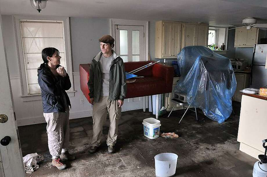 Bridget DiLauro and Connor Curtin stand in their South Water Street apartment which received major flooding. Photo by Peter Casolino/New Haven Register