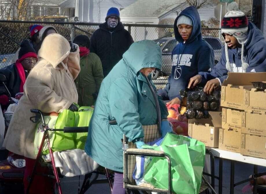 NEW HAVEN Hillhouse High School senior basketball players Bobby Bynum(L), and Christopher Leak Jr. , help distribute food at the Abdul Karim Hasan Islamic Center on Dixwell Ave.    Melanie Stengel/Register