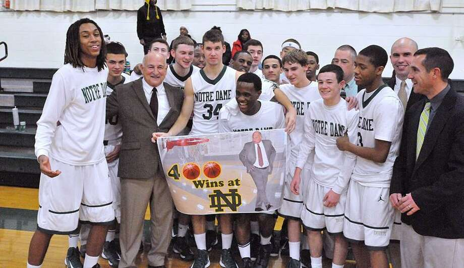 Notre Dame basketball coach Gary Palladino celebrates with his team after his 400th win Friday against berlin at home. Peter Casolino/Register.