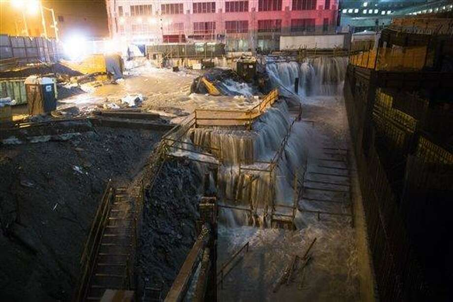 Sea water floods the Ground Zero construction site, Monday, Oct. 29, 2012, in New York. Sandy continued on its path Monday, as the storm forced the shutdown of mass transit, schools and financial markets, sending coastal residents fleeing, and threatening a dangerous mix of high winds and soaking rain. (AP Photo/ John Minchillo) Photo: ASSOCIATED PRESS / AP2012