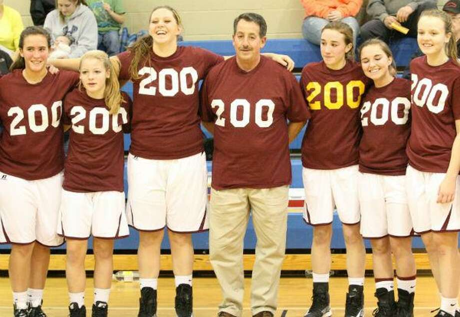 Dispatch Staff Photo by JOHN HAEGER Canastota girls basketball coach Vinny Salamone poses with his team after earning his 200th career victory Friday.