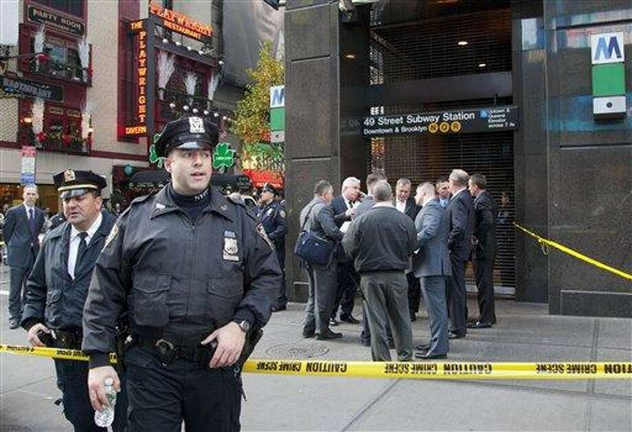 Uniformed and plainclothes police officers stand outside a New York subway station Dec. 3 after a man was killed after being pushed into the path of a train. Police are searching for a woman who killed a man Thursday by pushing him in front of a subway train. Associated Press file photo Photo: ASSOCIATED PRESS / AP2012