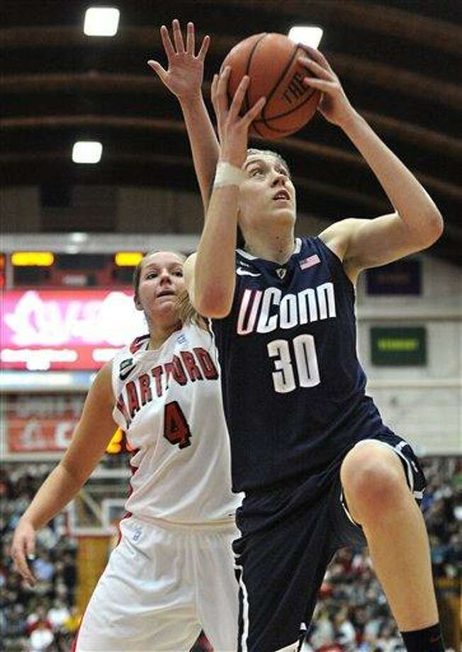 Connecticut's Breanna Stewart (30) goes up for a basket while guarded by Hartford's Christie Michals (4) during the second half of an NCAA women's college basketball game in West Hartford, Conn., Saturday, Dec. 22, 2012. Stewart was top scorer for Connecticut with 27 points in their 102-45 win over Hartford. (AP Photo/Jessica Hill) Photo: ASSOCIATED PRESS / A2012