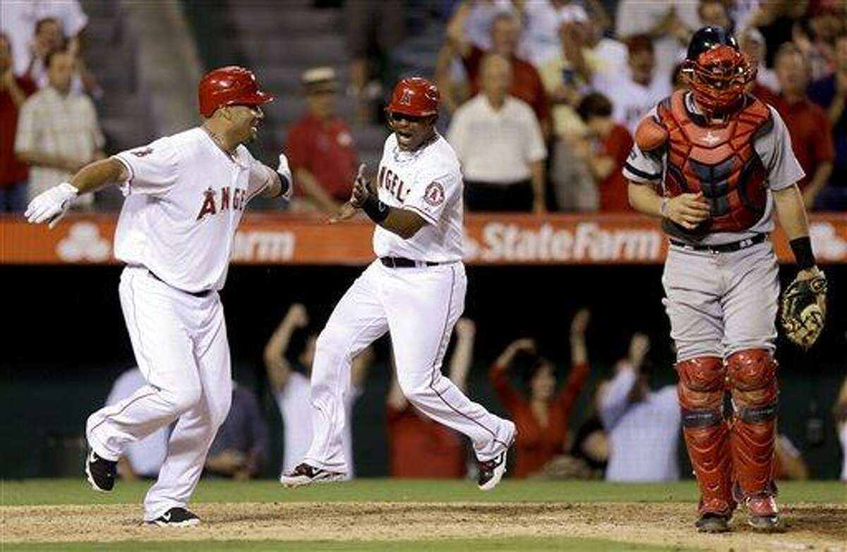 Los Angeles Angels' Albert Pujols, left, and Alberto Callaspo celebrate Torii Hunter's game winning sacrifice fly as Boston Red Sox catcher Ryan Lavarnway looks away during bottom of the ninth inning of an baseball in Anaheim, Calif. Tuesday, Aug. 28, 2012 (AP Photo/Chris Carlson)