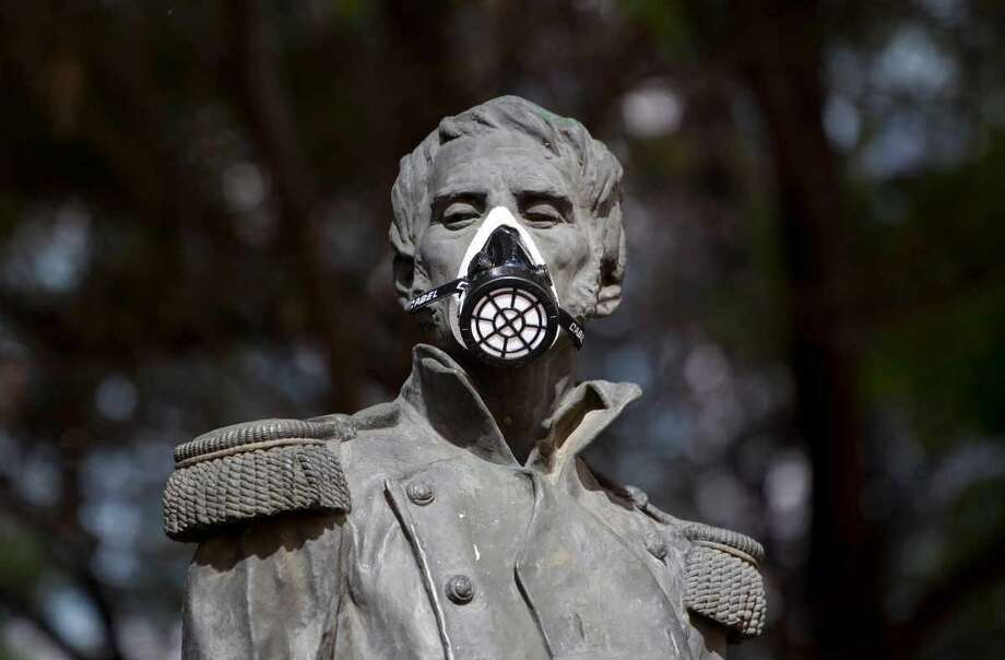 A gas mask covers the mouth on the statue of independence hero Leonardo Bravo in Mexico City Tuesday. Activists are protesting pollution by placing gas masks on statues of Mexican heroes. Associated Press Photo: ASSOCIATED PRESS / AP2012
