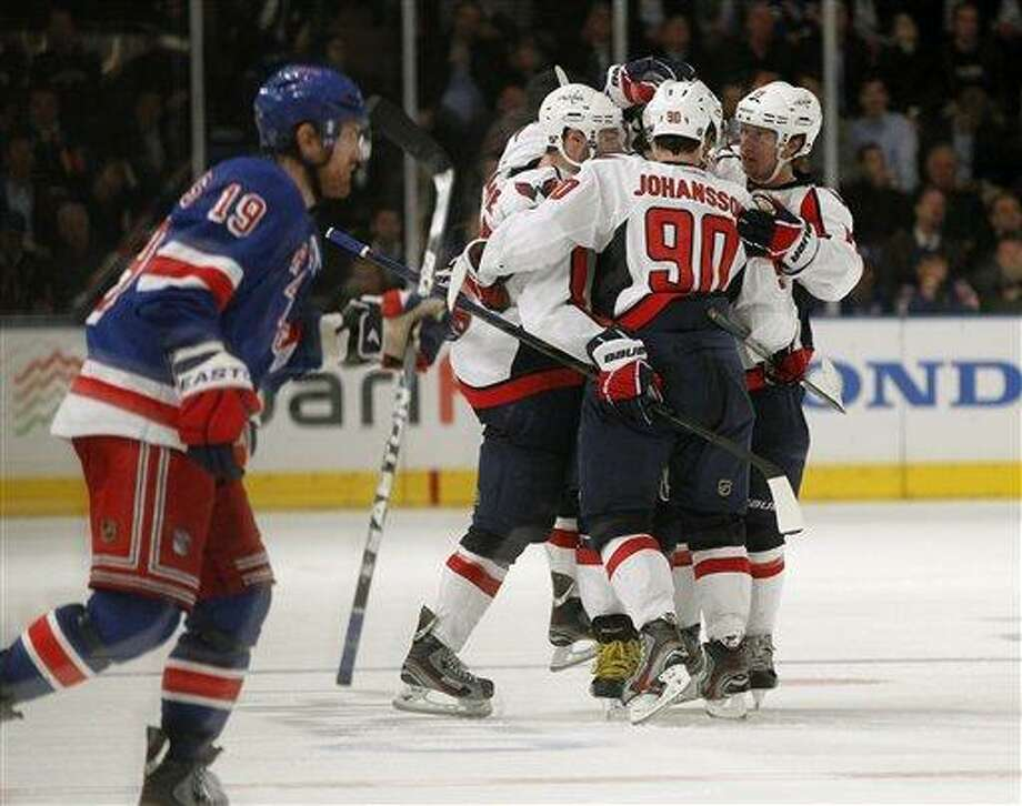 New York Rangers center Brad Richards (19) skates away as Washington Capitals celebrate around teammate Alex Ovechkin, after Ovechkin scored the winning goal in the third period of Game 2 of the NHL Eastern Conference semifinals at Madison Square Garden in New York, Monday, April 30, 2012. The Capitals defeated the Rangers 3-2. (AP Photo/Kathy Willens) Photo: AP / AP