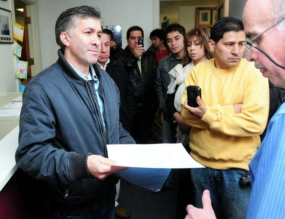 Herman Zuniga (left) president of Community Immigrants of East Haven, hands a letter to Frank Gentilesco, Jr. (right), assistant director of administration and management, for East Haven Mayor Joseph Maturo, Jr., at East Haven Town Hall on 3/1/2012. Photo by Arnold Gold/New Haven Register