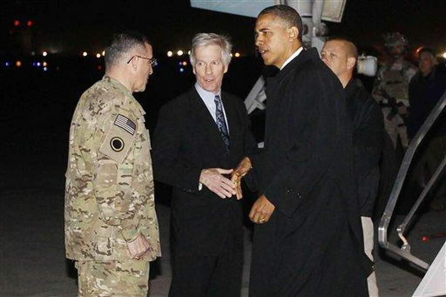 """President Barack Obama is greeted by Lt. Gen. Curtis """"Mike"""" Scaparrotti, and U.S. Ambassador to Afghanistan Ryan Crocker as he steps off Air Force One at Bagram Air Field in Afghanistan, Tuesday, May 1, 2012. (AP Photo/Charles Dharapak) Photo: AP / AP"""