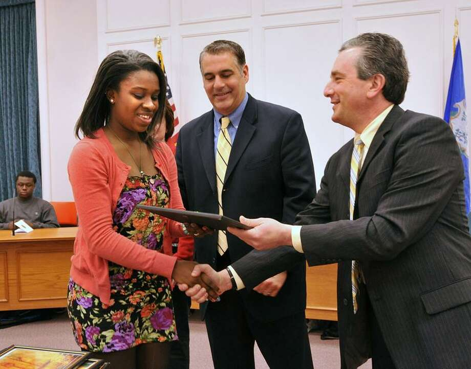 Ebonie Routh, a West Haven High School junior, receives an award for leadership during the 17th annual Black Heritage Celebration at West Haven City Hall. Giving the award is Superintendent Neil Cavallaro, right, and Mayor John M. Picard. Peter Casolino/Register