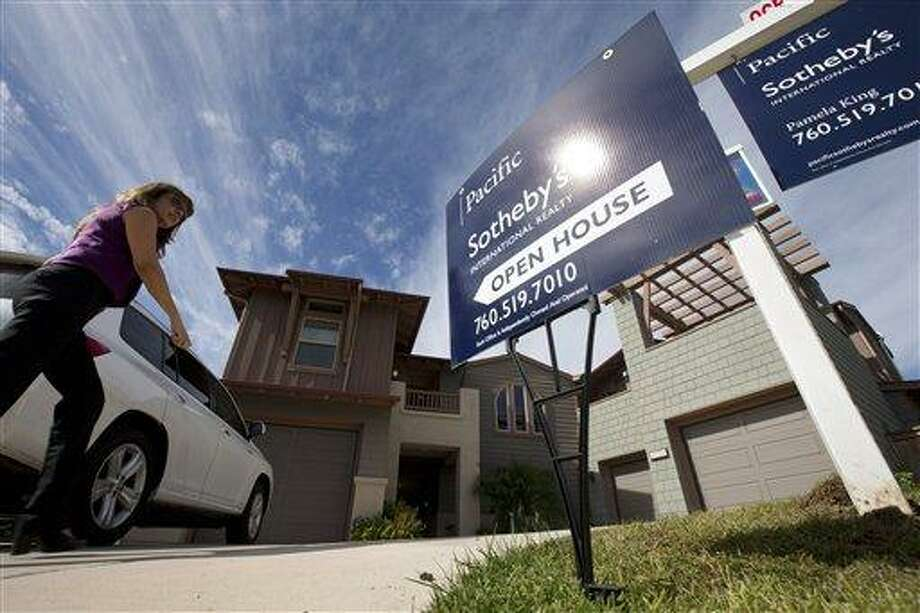 In this Wednesday, Nov. 14, 2012, photo, a woman walks towards a home for sale during a viewing for brokers in Leucadia, Calif. Americans bought new homes in November 2012 at the fastest pace in more than two and a half years, further evidence of a sustained housing recovery.(AP Photo/Gregory Bull, File) Photo: AP / AP