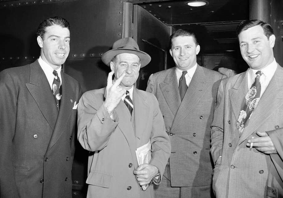 """New York Yankee manager Stanley """"Bucky"""" Harris, second from left, holds up tow fingers, signifying his intention of bringing his team home in front for the second consecutive season, as Harris, Joe DiMaggio, left, Frank """"Specs"""" Shea, second from right, and Joe Page leave New York, Feb. 28, 1948 from Pennsylvania Station, New York City. The team is en route to St. Petersburg, Fla. for spring training. (AP Photo/Harry Harris) Photo: ASSOCIATED PRESS / AP1948"""