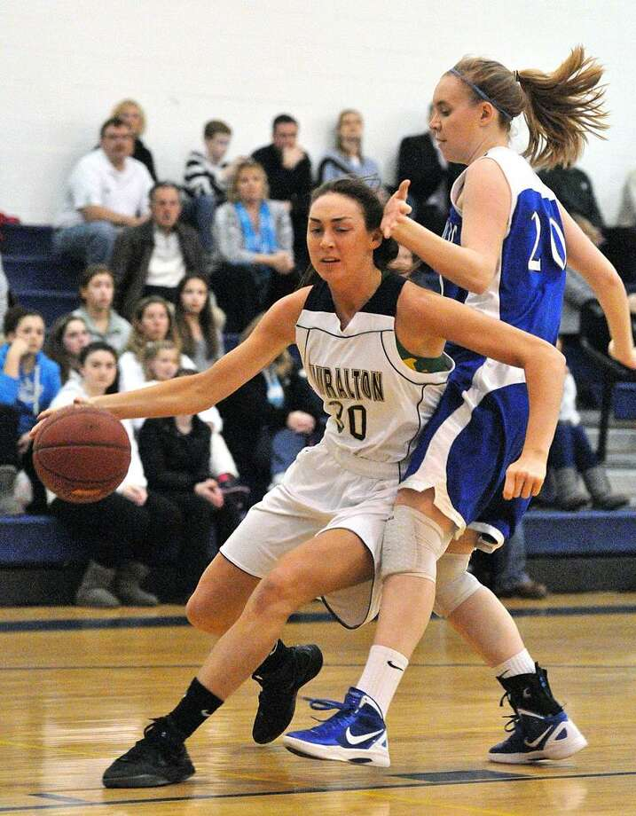 Milford-- Lauralton Hall's Catherine Gildea drives past East Catholic's Nicole Ferguson during the first quarter .   Photo- Peter Casolino/New Haven Register 03/01/12